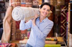 98079402 - woman holding carpet  before buying to her new house interior